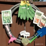 Repurposed Garden Hose Wreath - festive gardening themed wreath made from an old hose and some colorful kids gardening tools.