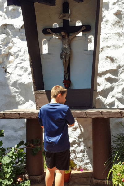boy in front of cross san diego mission