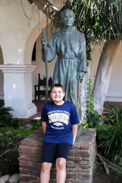 mission san diego boy in front of statue of Father Junipero Serra